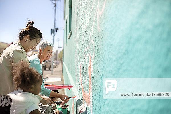 Female volunteers painting mural on sunny wall