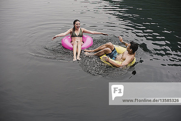 Young couple floating on lake in inflatable rings
