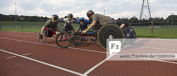 Determined paraplegic athletes bonding in huddle  training for wheelchair race on sports track