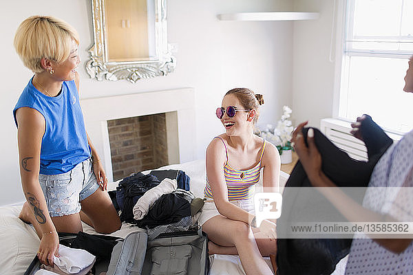 Carefree young women friends packing for spring break in bedroom