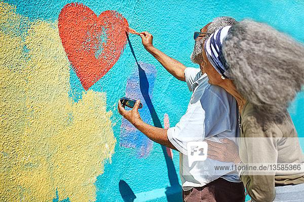 Senior couple painting heart-shape mural on sunny wall