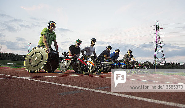 Portrait confident  determined paraplegic athletes training for wheelchair race on sports track