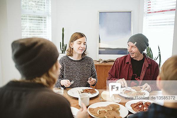 Family enjoying pancake breakfast at table