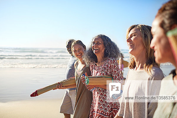 Happy friends with yoga mats on sunny beach during yoga retreat