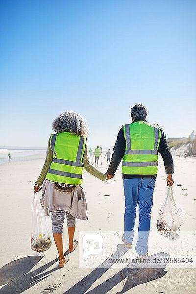 Affectionate senior couple volunteers cleaning up litter on sunny  wet sand beach
