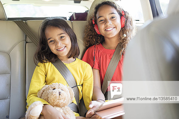 Portrait happy sisters with teddy bear riding in back seat of car