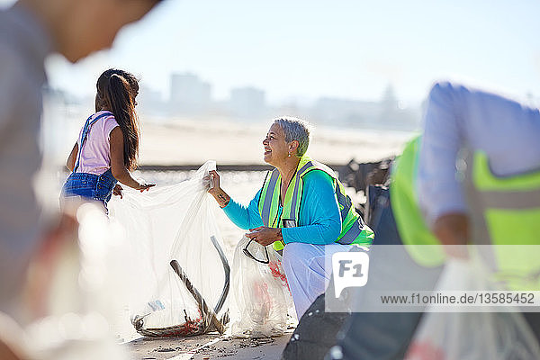 Senior woman and girl volunteer cleaning up litter on sunny beach