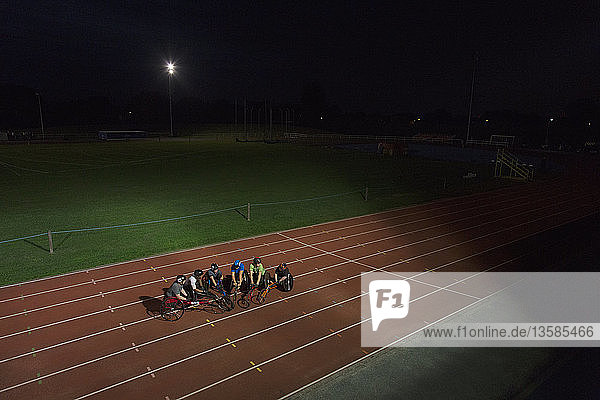 Paraplegic athletes on sports track  training for wheelchair race at night