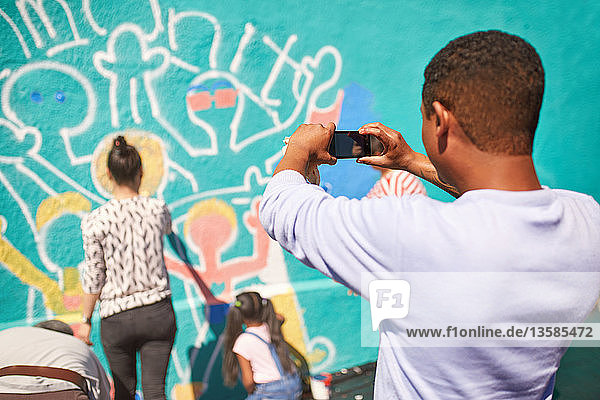 Man with camera phone photographing community mural on sunny wall