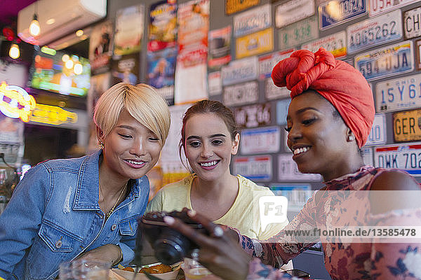 Young women friends using digital camera in bar