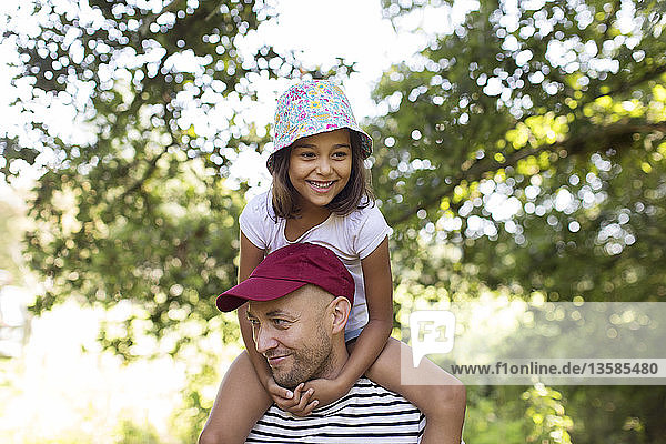Father carrying daughter on shoulders in park