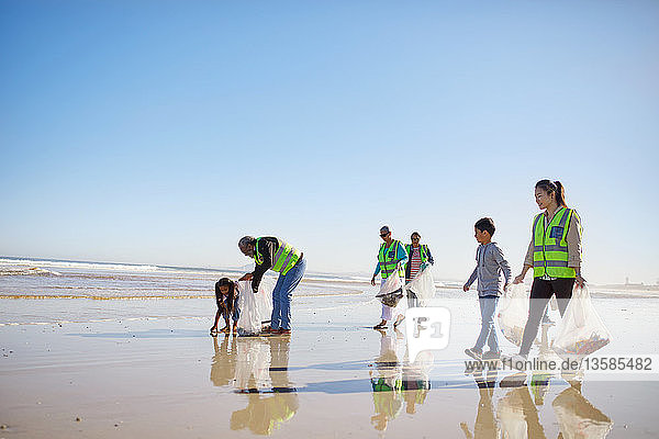 Volunteers cleaning litter from wet sand beach