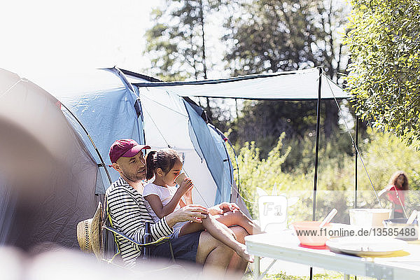 Father and daughter relaxing at campsite