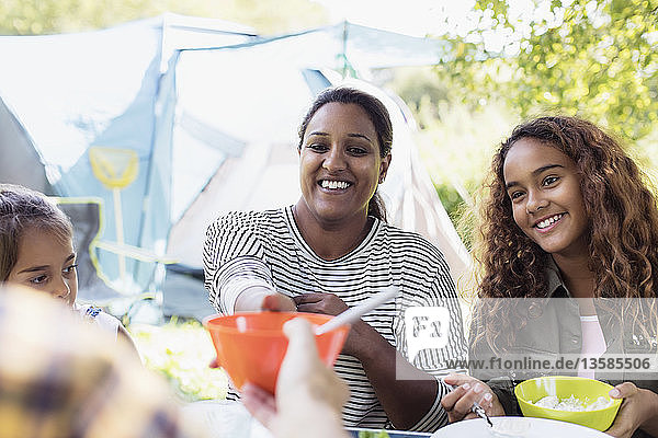 Smiling mother and daughters enjoying lunch at campsite