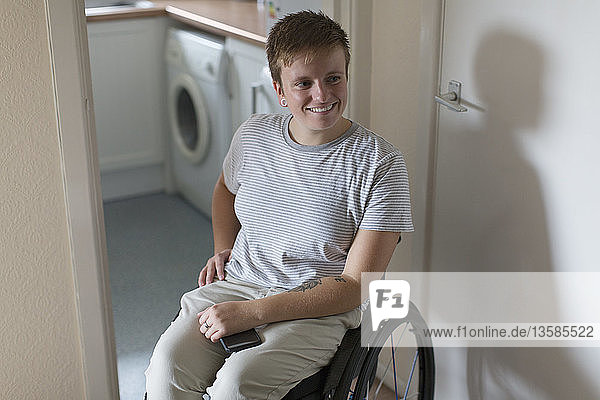 Smiling young woman in wheelchair at home