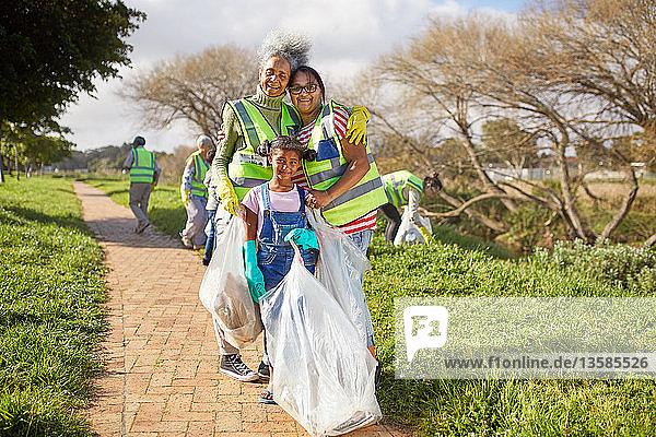 Portrait happy multi-generation women volunteering  cleaning up litter in sunny park