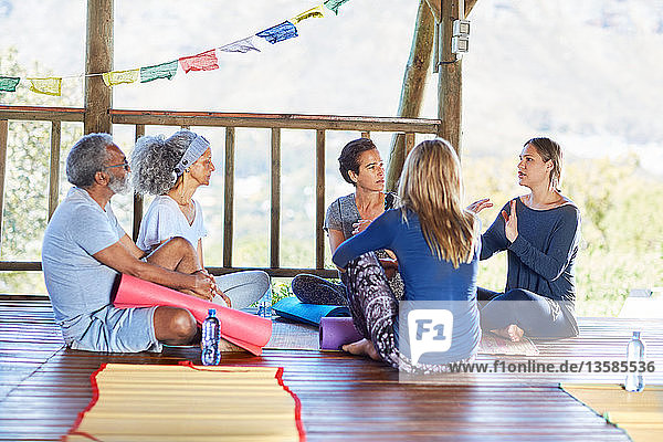 Yoga class talking in circle in hut during yoga retreat