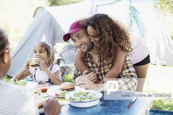 Affectionate daughter hugging father eating lunch at campsite