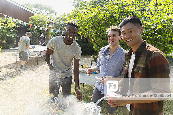 Portrait smiling male friends enjoying summer backyard barbecue