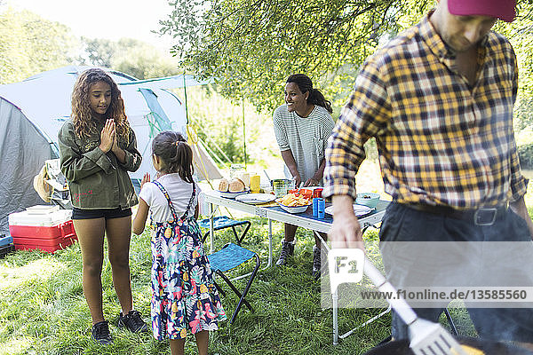 Family preparing barbecue lunch at campsite