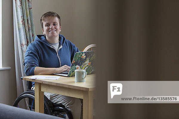 Portrait smiling  confident young woman in wheelchair at laptop