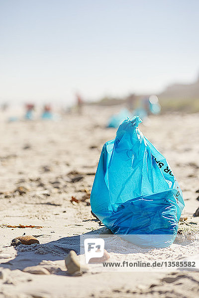 Blue cleanup garbage bag on sunny  sandy beach