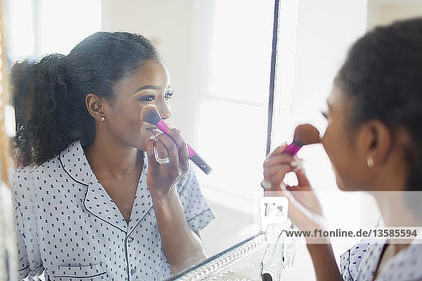Young woman getting ready  applying makeup in bathroom mirror
