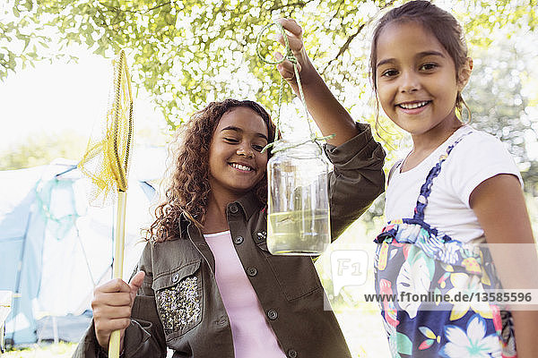 Portrait happy sisters catching fish in jar