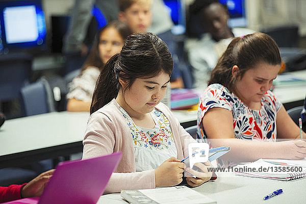 Focused junior high school girl student using digital tablet in classroom