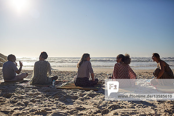 Yoga class talking on sunny beach during yoga retreat