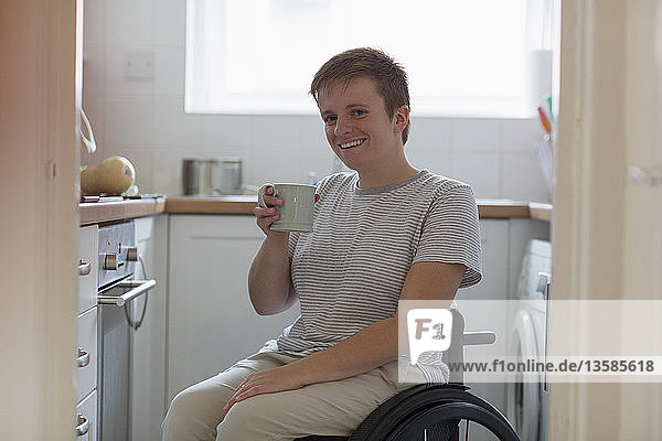 Portrait smiling  confident young woman in wheelchair drinking tea in apartment kitchen
