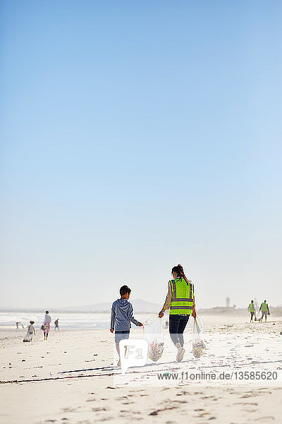 Mother and son volunteers cleaning up litter on sunny  sandy beach
