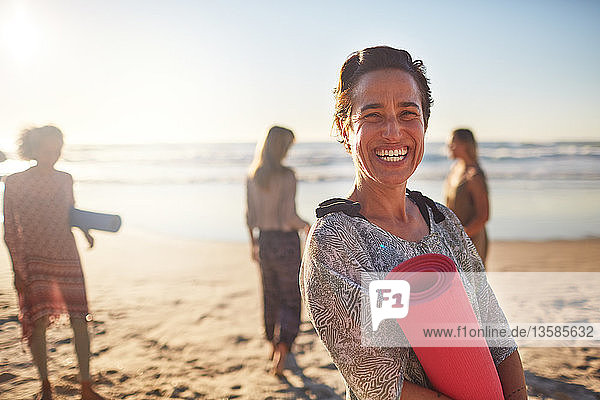 Portrait happy woman with yoga mat on sunny beach during yoga retreat