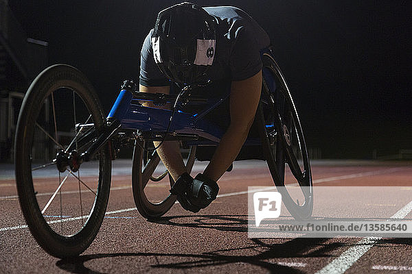 Tired paraplegic athlete resting on sports track after wheelchair race at night