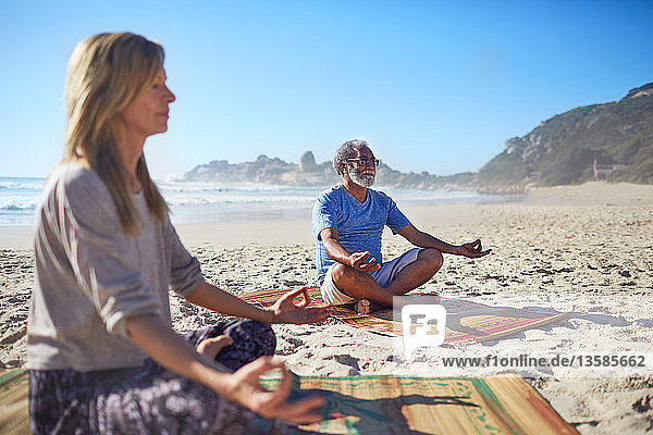 Serene people meditating on sunny beach during yoga retreat