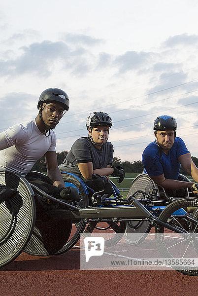 Portrait confident  determined paraplegic athletes training for wheelchair race on sports track