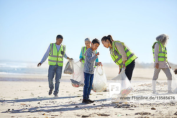 Volunteers cleaning up litter on sunny  sandy beach