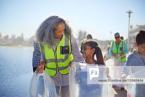 Grandmother and granddaughter volunteers picking up litter on boardwalk
