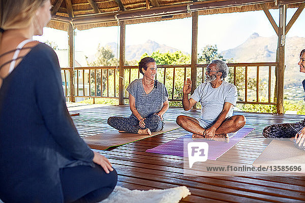 Man and woman talking during yoga class in hut on yoga retreat