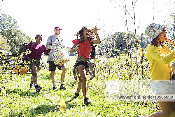 Eager family carrying camping equipment in sunny field