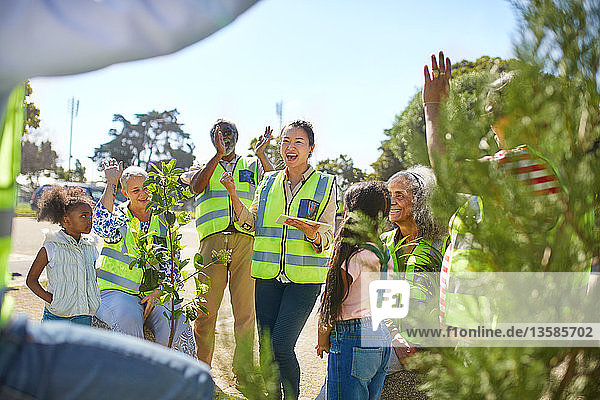 Enthusiastic volunteers cheering  planting trees at sunny park