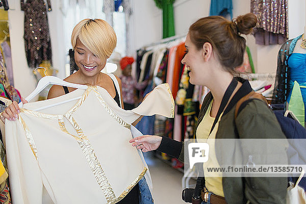 Young women friends shopping in clothing store