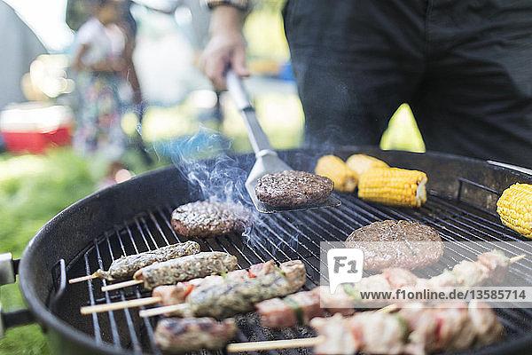 Man barbecuing hamburgers  kebabs and corn cobs