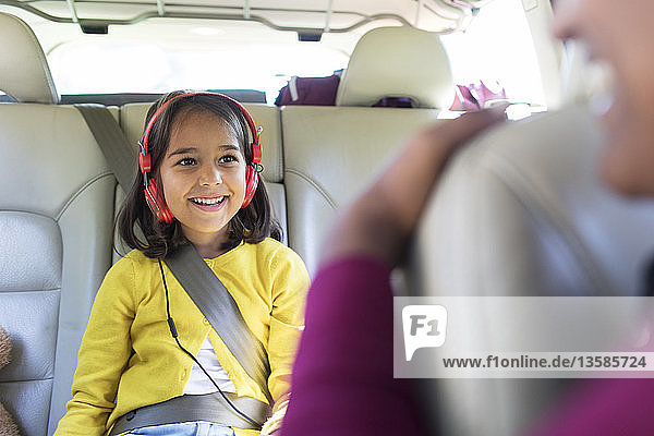 Smiling girl with headphones riding in back seat of car