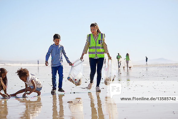 Mother and son volunteers cleaning up litter on sunny wet sand beach