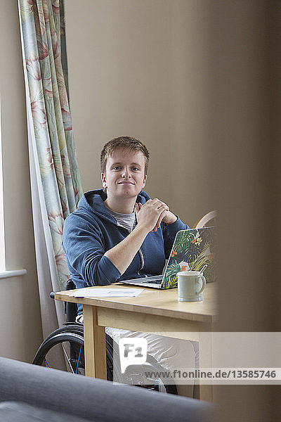 Portrait confident young woman in wheelchair using laptop at dining table