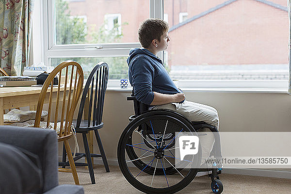 Thoughtful young woman in wheelchair looking out window