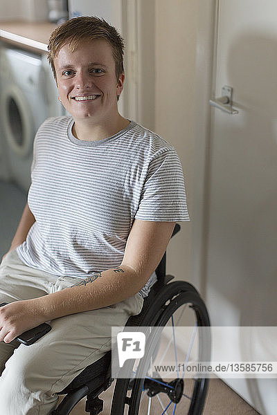 Portrait smiling  confident young woman in wheelchair at home