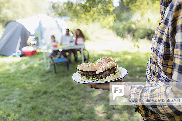 Father serving barbecue hamburgers to family at campsite