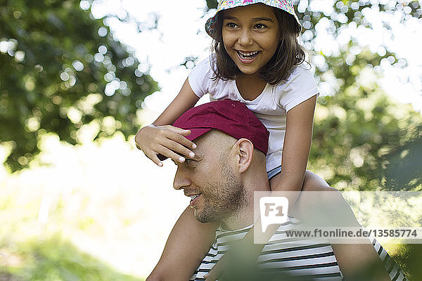 Father carrying happy daughter on shoulders